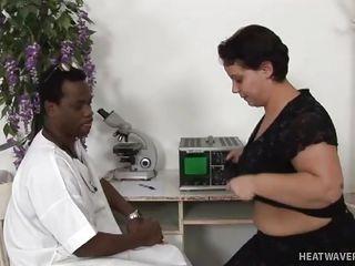 black doctor examines woman's big milk cans