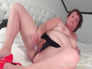 Aged slut pleasuring her pussy in daybed