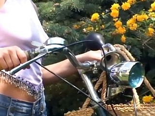 Biking honey plays with her pink dildo outside on a blanket